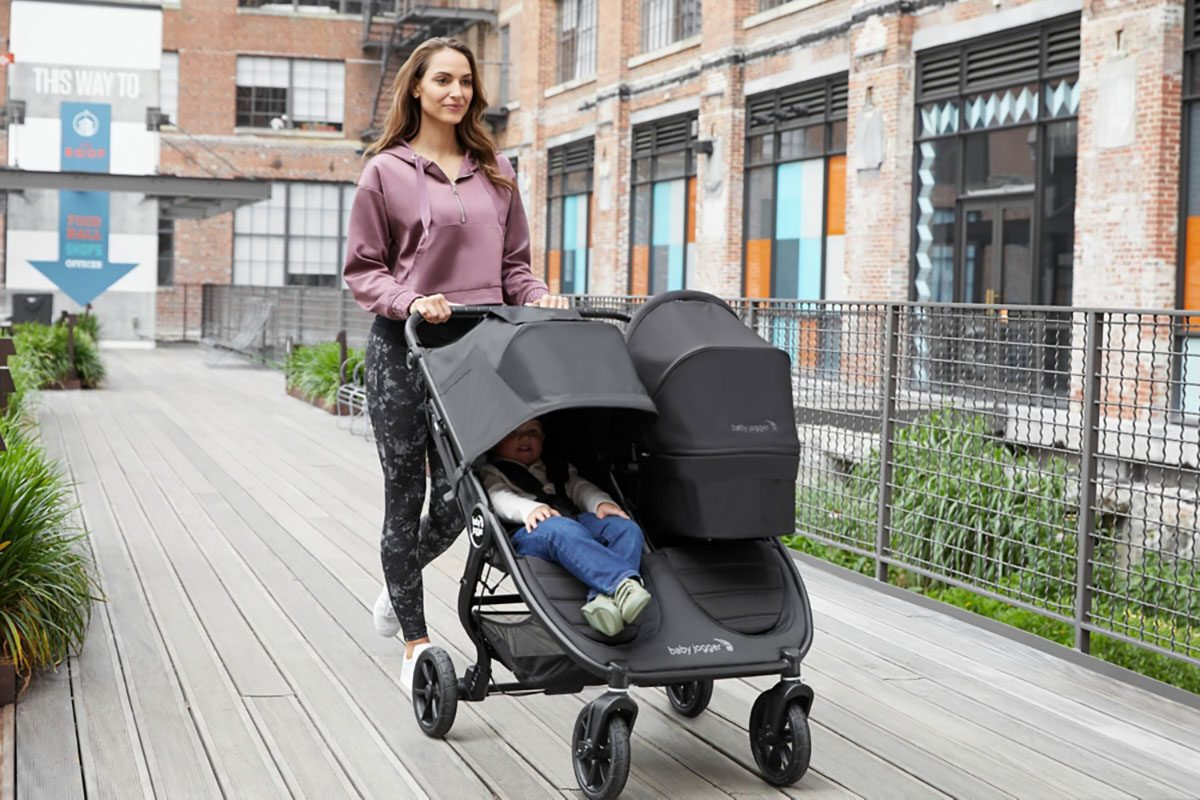 Mother pushes twin children in Baby Jogger City Mini GT double stroller
